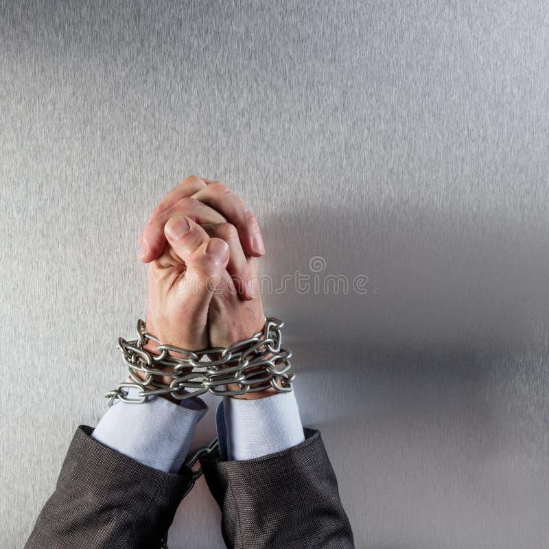 Manos unidas del hombre de negocios atadas con la cadena que ruega para el crimen corporativo fotografía de archivo libre de regalías