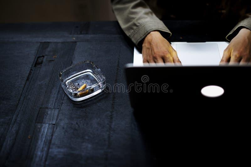Manos usando el ordenador portátil del ordenador por la bandeja de ceniza de cigarrillo imagen de archivo libre de regalías