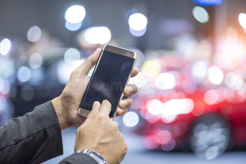 Manos usando smartphone digital con el coche inteligente imagenes de archivo