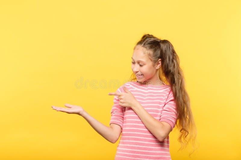 Manos vacías sonrientes del objeto virtual del punto de la mirada de la muchacha foto de archivo libre de regalías