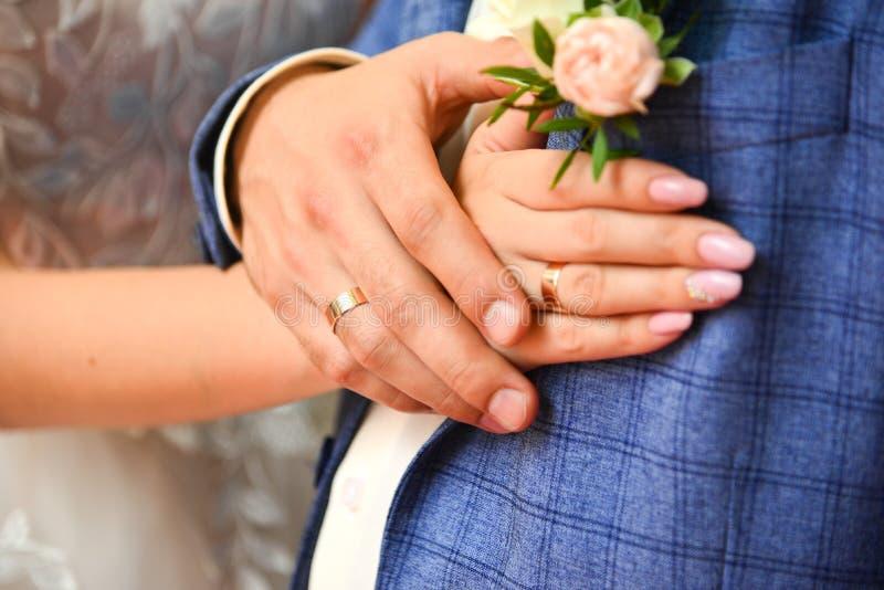 Manos y anillos en casarse pálido - boutonniere de la rosa del rosa fotografía de archivo libre de regalías