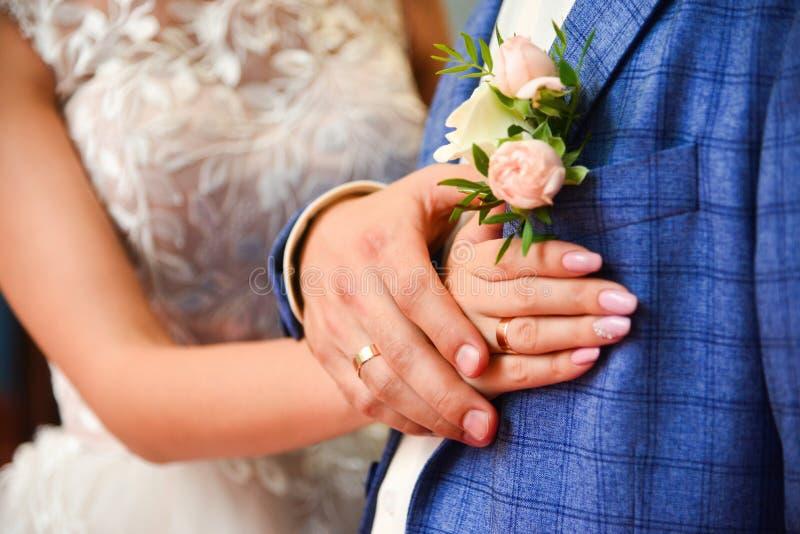 Manos y anillos en casarse pálido - boutonniere de la rosa del rosa, cierre para arriba fotografía de archivo