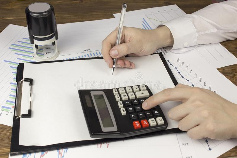 Manos y calculadora masculinas, documentos en la oficina, hombre de negocios masculino, primer imagen de archivo