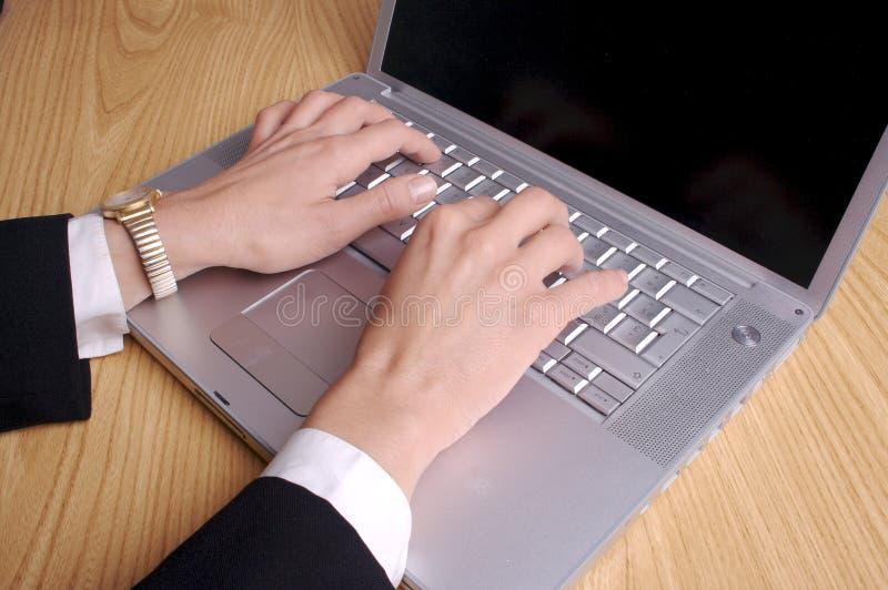 Manos y computadora portátil imagen de archivo