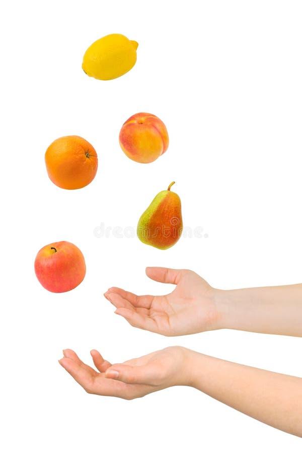 Manos y frutas que hacen juegos malabares imagen de archivo