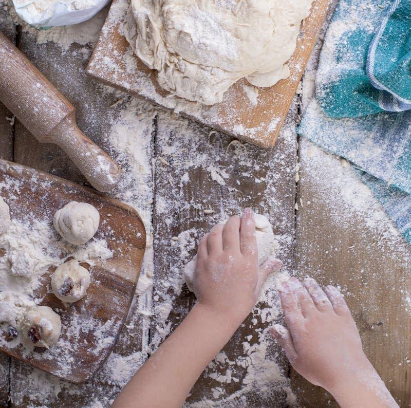 Manos y pasta del ` s de los niños con la harina en una tabla de madera y una toalla, un rodillo y un tablero verdes imagen de archivo