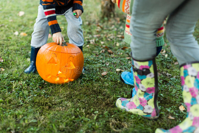 Manos y piernas de los niños que ponen la tapa en la calabaza de Halloween imagenes de archivo