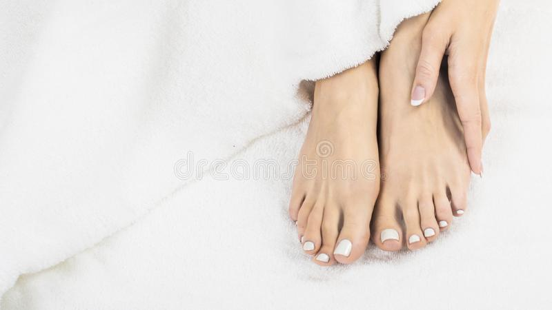 Manos y pies hermosos de mujeres sanas en cama imagen de archivo