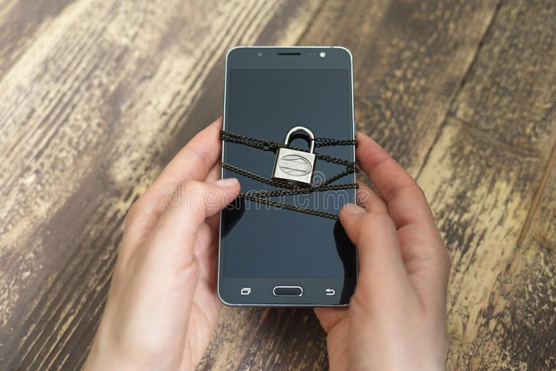 Manos y smartphone de la mujer atados con la cadena y el candado metálicos imagen de archivo