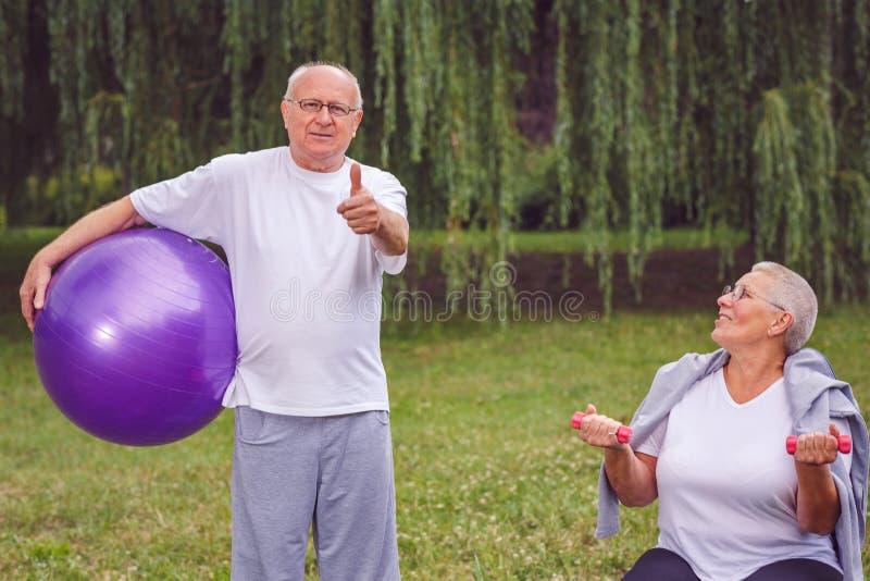 Manosee con los dedos para arriba para el ejercicio sano - los pares mayores felices con el fitne foto de archivo libre de regalías