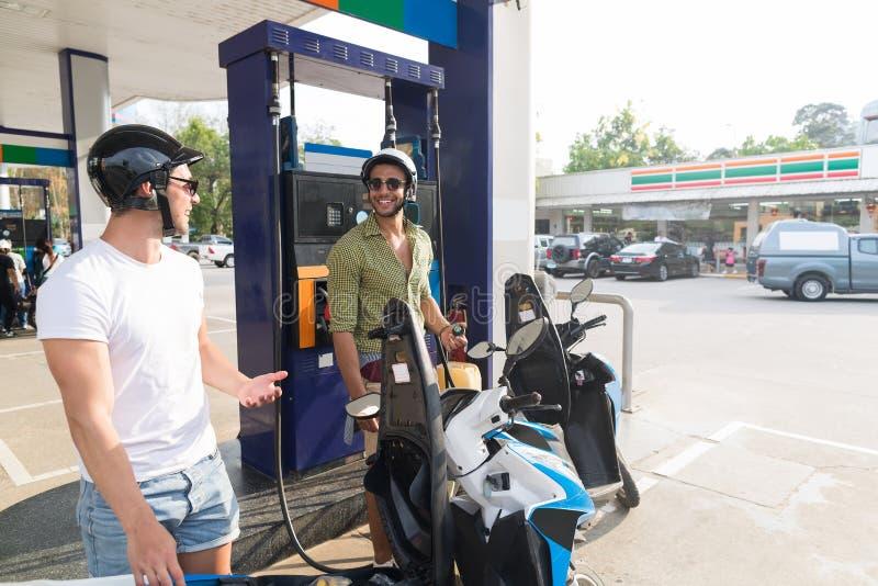 Manpar på cykeln för bensinstationbränslemotor, lyckligt le resa för grabbar royaltyfria foton
