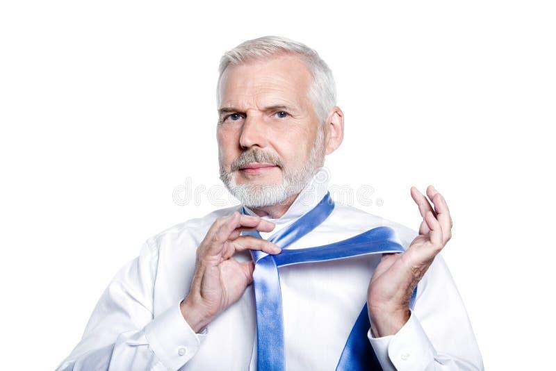 Manpensionär som får klädd binda windsorslipsen royaltyfri fotografi