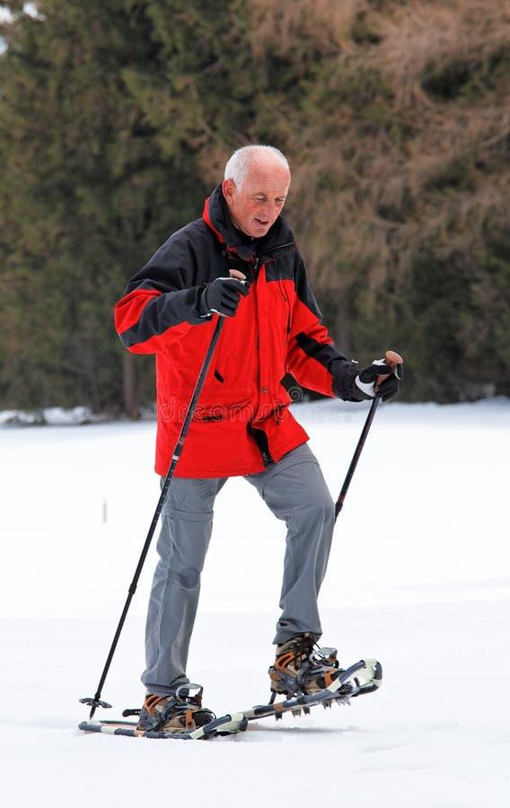 Manpensionär som snowshoeing