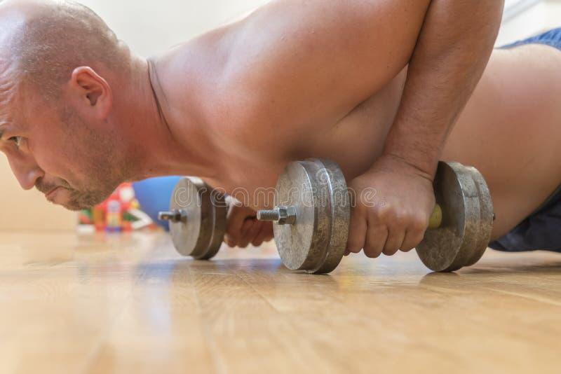 Manpressarna från golvet close upp Begreppet av en sund livsstil och sport Den skalliga mannen går in för sportar royaltyfri foto