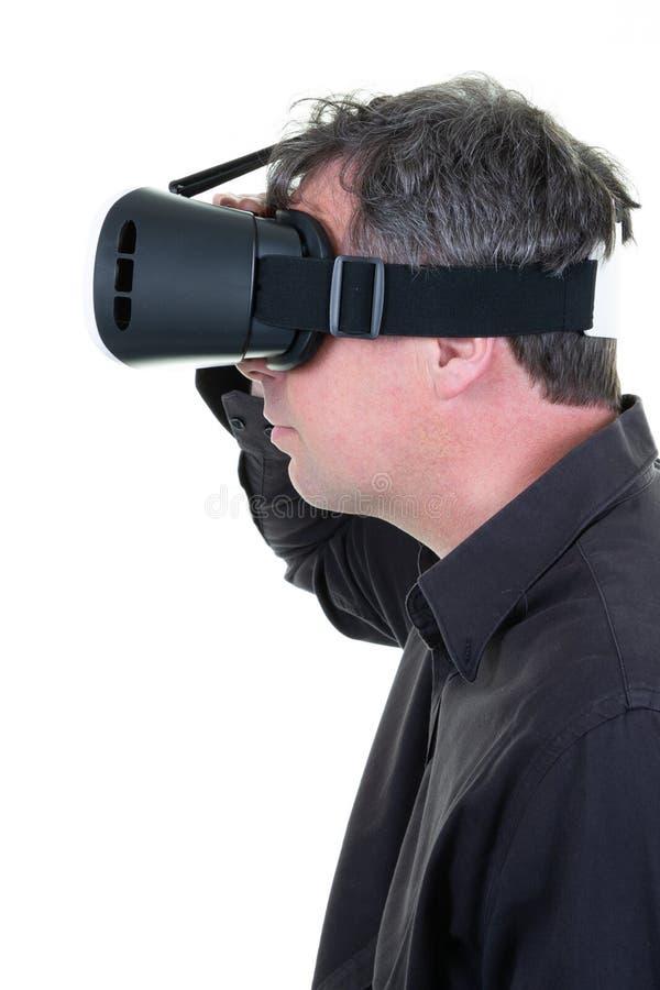 Manprofil genom att använda virtuell verklighethörlurar med mikrofon arkivfoto