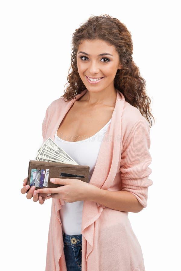 Manque d'argent. Jeunes femmes heureuses jugeant une bourse pleine de l'argent W photographie stock libre de droits