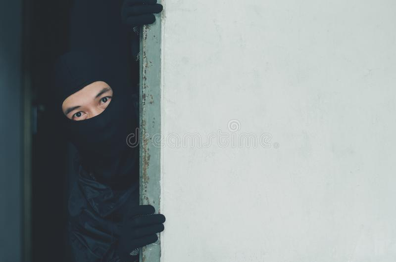 Manrånare, tjuv i maskeringen som döljer bak en tom vägg med utrymme för text arkivfoton