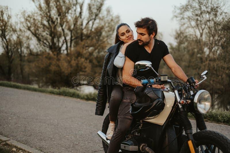 Manridningmotorcykel med flickvännen bak honom som ler royaltyfri bild