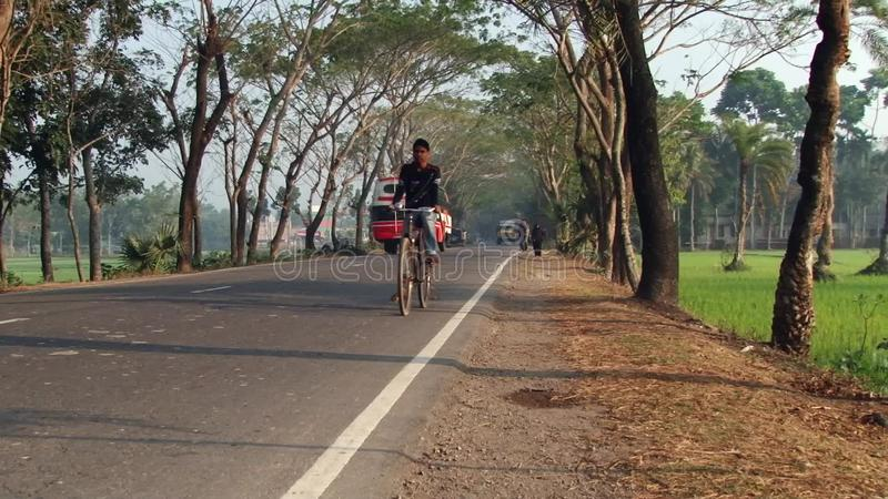 Manritter cyklar förbi vägen i Jessore, Bangladesh arkivfilmer