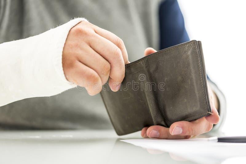Mans armen i en gipsförband som rymmer en plånbok royaltyfri foto