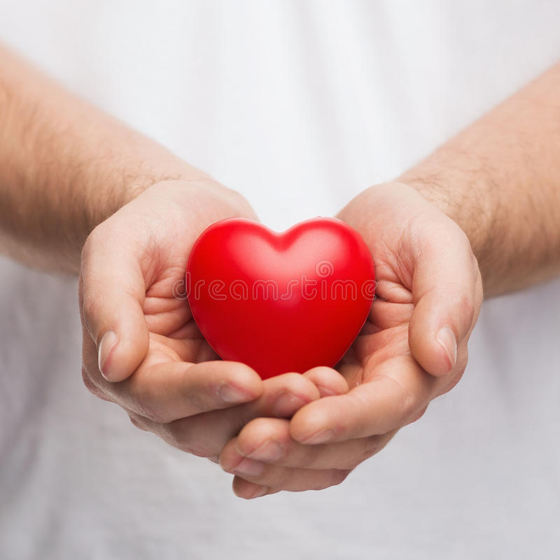 Mans cupped hands showing red heart. People, relationship and love concept - close up of mans cupped hands showing red heart stock photography