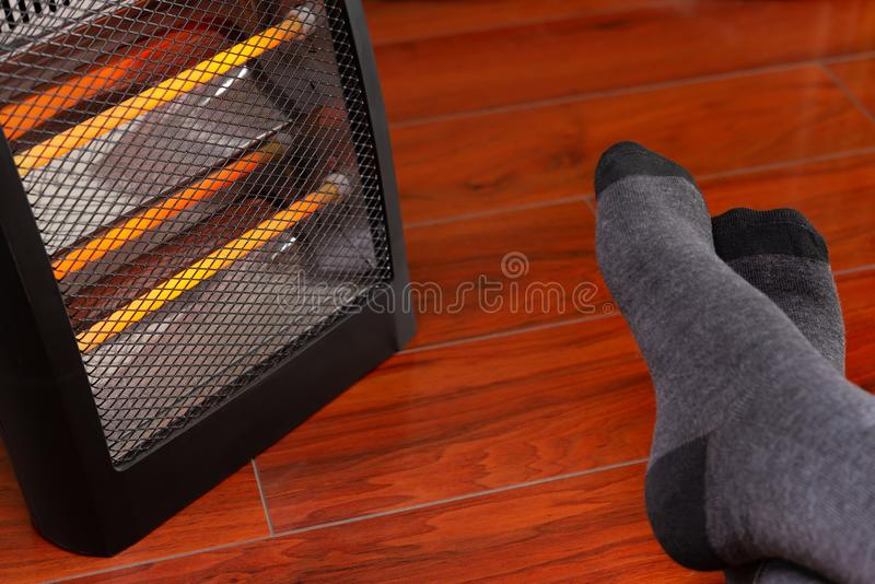 Mans feet in front of an electric heater royalty free stock photos