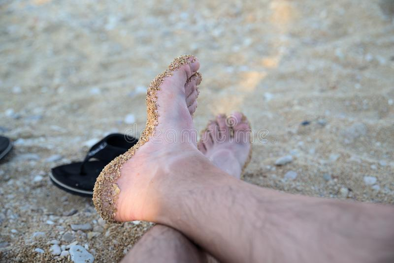 Mans foot covered with sand on the sandy beach. During summer holidays in Croatia royalty free stock image