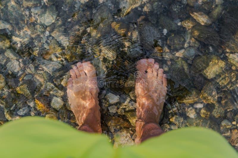 Mans fot i kallt klart vatten i sjömaggioren royaltyfri foto