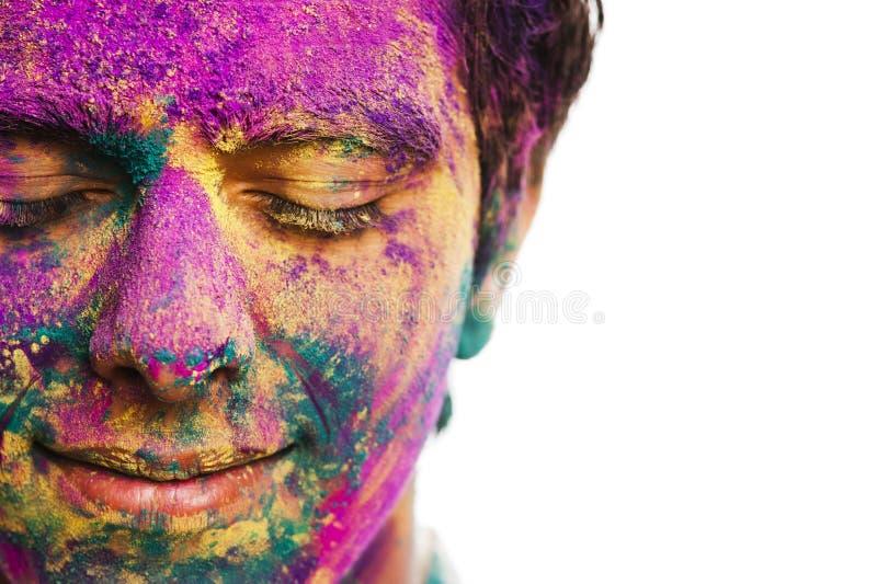 Mans framsida som täckas med pulvermålarfärg under den Holi festivalen arkivbilder
