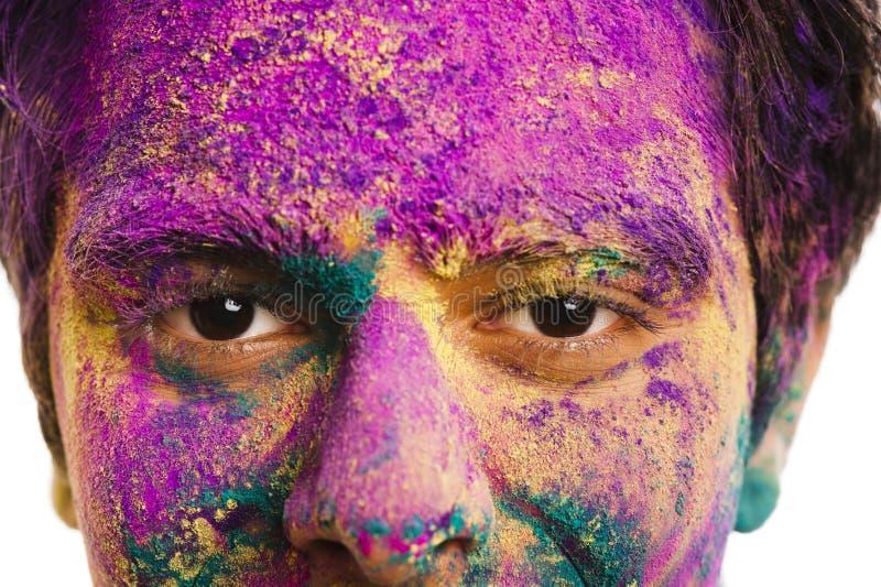 Mans framsida som täckas med pulvermålarfärg under den Holi festivalen arkivfoto