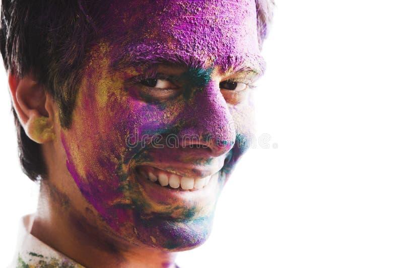 Mans framsida som täckas med pulvermålarfärg under den Holi festivalen royaltyfria bilder