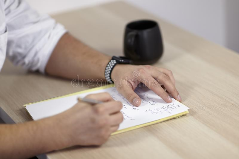 Mans händer på den vita dräkten skriver med rullpennan på papperet på trätabellen någon latin eller medicinuttryck Kopp te royaltyfri foto