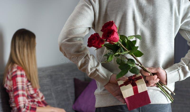 Mans händer som döljer rymma den chic buketten av röda rosor, och gåvan med det vita bandet bak baksida och kvinnan med det vända arkivfoto