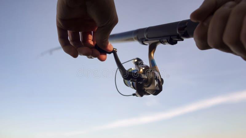 Mans händer som rotera fiska rullen som fångar upp fisken, kugghjulet och tillförsel, slut royaltyfria foton