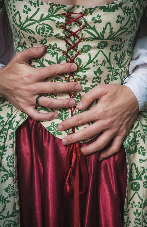 Mans händer som rymmer kvinnan i medeltida klänning royaltyfri foto
