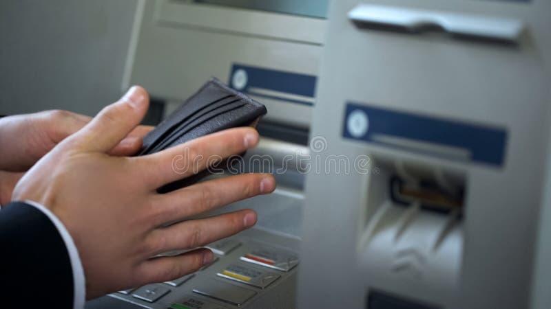 Mans händer som sätter euro i plånboken, kassa som återtas från ATM som utomlands reser royaltyfri bild