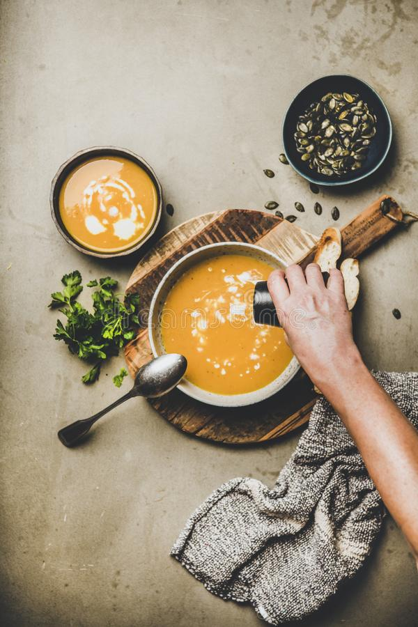 Mans hand adding pepper to pumpkin cream soup with seeds royalty free stock photo