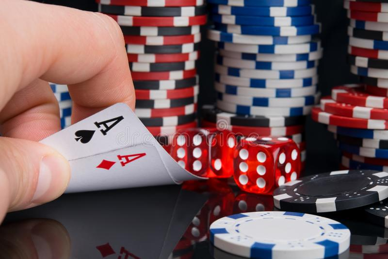 The man`s hand, on a black table with a reflection, opens the two highest cards in the game twenty-one, against the background of stock photos