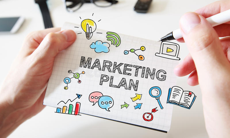 Mans hand drawing Marketing Plan concept on notebook stock images