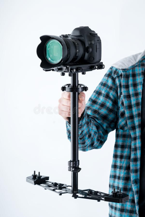 Mans hand holding camera stabiliser with digital camera on top. Glidecam, steady cam, professional equipment stock photos