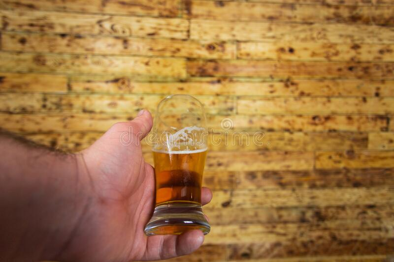 Mans hand holding glass of beer. Wood background stock image