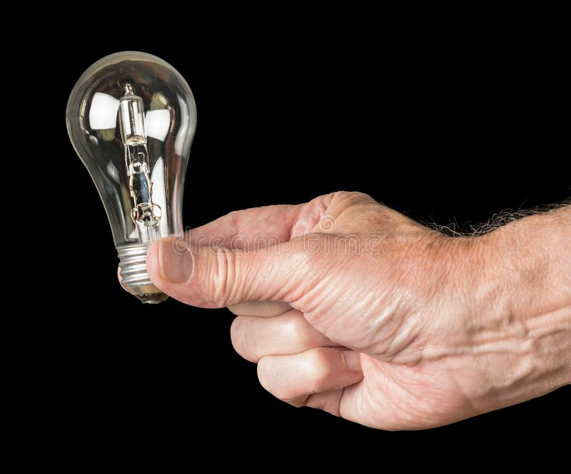 Mans hand holding a halogen lightbulb soon to be banned in the EU. The European Union is banning the sale and manufacture of halogen light bulbs because they are royalty free stock photos