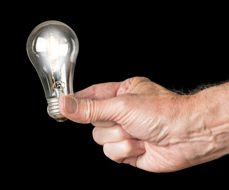 Mans hand holding an illuminated halogen lightbulb. The European Union is banning the sale and manufacture of halogen light bulbs because they are too royalty free stock image