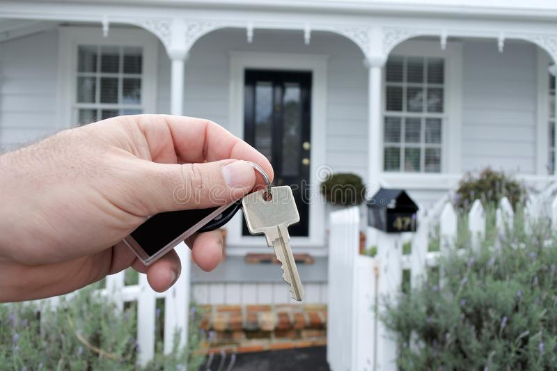 A mans hand holds a key against a house in Auckland New Zealand. A mans hand holds a key against a front of a traditional villa house in Auckland, New Zealand royalty free stock photo