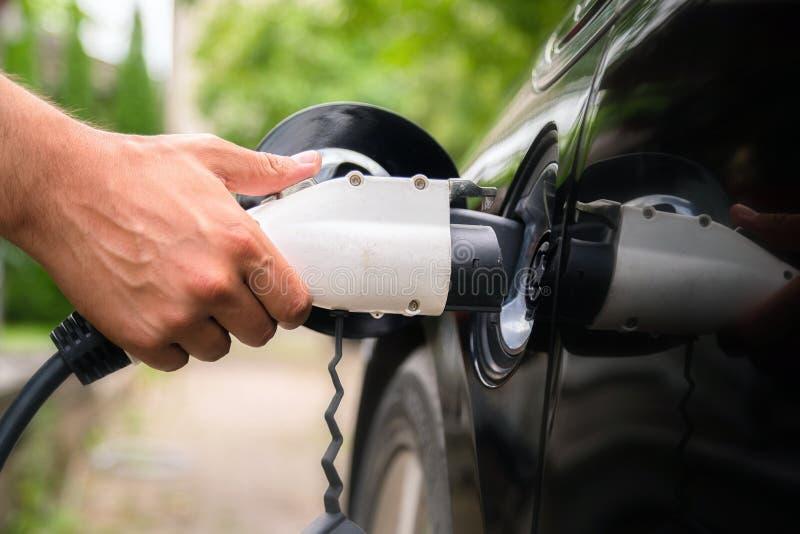 Mans hand inserindo plugue carregador no carro elétrico em ambiente verde Novo veículo de energia, NEV está sendo carregado com fotografia de stock