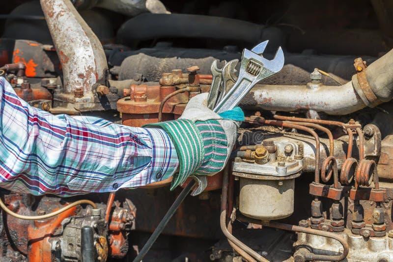 Mans hand med den justerbara skiftnyckeln nära den gamla dieselmotorn royaltyfria foton