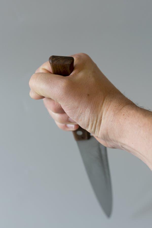 Mans hand med en kniv p? gr? bakgrund Begrepp av v?ld Hand av en gangster med en kniv Vertikalt foto arkivbilder