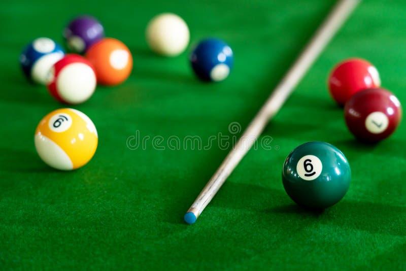 Mans hand och stickreplikarm som spelar snookerleken eller förbereder att sikta att skjuta pölbollar på en grön billiardtabell arkivfoton