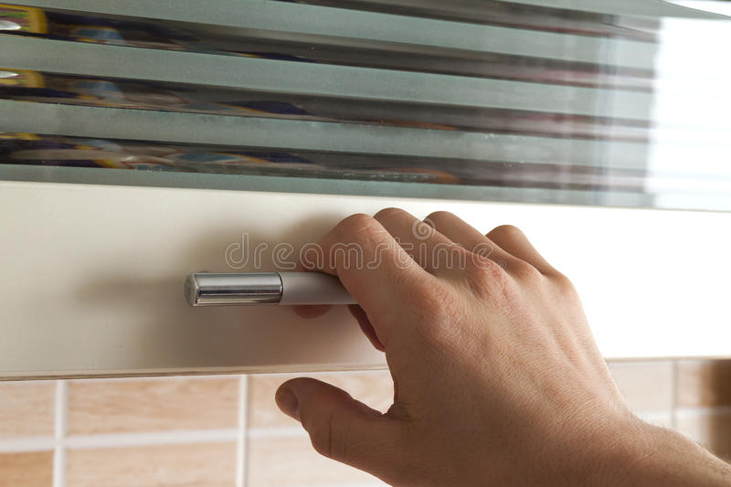 Mans hand open the kitchen cupboard doors, close up royalty free stock photos