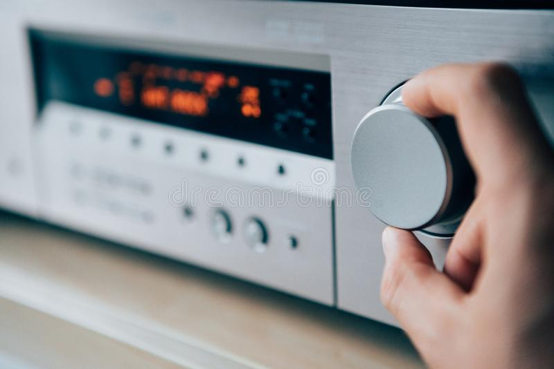 Mans hand rotating the Amplifier Volume regulator Adjusting the royalty free stock image